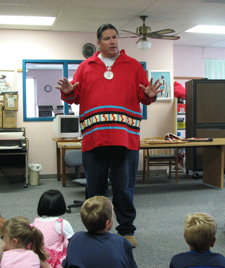 Telling a tall tale, Assistant Curator Lewis Johnson entertains children at the Holdenville Public Library with a Seminole legend during a summer reading program.